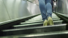 4K Female legs in jeans on a moving escalator in slow motion, shot on RED EPIC Stock Footage
