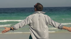 Man with wide open arms on beach enjoying sunny day, slow motion shot at 240fps Stock Footage