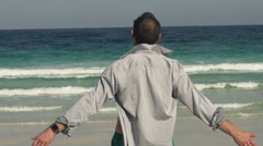 Man with wide open arms on beach enjoying sunny day Stock Footage