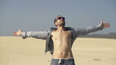 Young man with wide open arms on desert enjoying sunny day Stock Footage