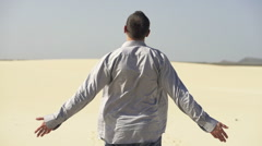 Man with wide open arms on desert enjoying sunny day, slow motion shot at 240fps Stock Footage