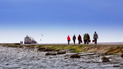 Anonymous people walking on a mole. Background containerships. Stock Footage
