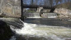 Retro tumbledown bridge over river waterfall water flowing. 4K Stock Footage