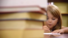 Stock Video Footage of School Girl Writing on Paper at Library with Books