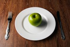 table appointments and the fresh green apple on a white plate - stock photo