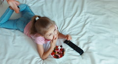 Lonely child girl switching TV lying on the bed. Child shocked TV. Child eating Stock Footage