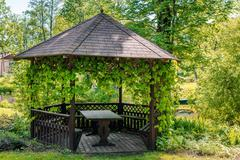 Wooden gazebo over summer landscape Stock Photos