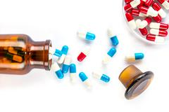 blue capsules and red capsules with  bottle, healthcare and medicine - stock photo
