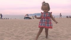 Beautiful baby in a red blue dress   throws sand foot into the camera Stock Footage