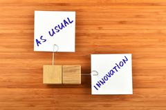 Innovation, two paper notes with wooden holders on wood - stock photo