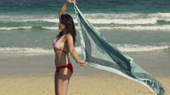 Young, pretty woman with pareo walking along beach Stock Footage