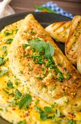 Herb omelette with chives and oregano sprinkled with chili flakes, garlic pan - stock photo