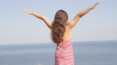 Stock Video Footage of girl standing on a sea beach arms outstretched