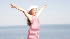 Stock Video Footage of girl in white hat stands on the sea beach arms outstretched