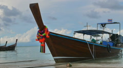 Beautiful decorated longtail boat moored at the sandy beach Stock Footage