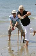 Man and woman playing cricket at the seaside retired couple enjoying healthy Stock Photos