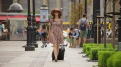 Happy young woman tourist is walking on a city street with tickets and suitcase - stock footage