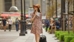 Young woman with tourist map walking on street, asking passer-by for direction Stock Footage