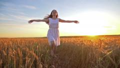 A young girl smiles happily and runs across the field of Golden wheat at sunset Stock Footage