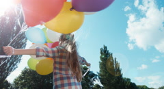 Girl 6-8 years old spinning with balloons against the sky in the sunlight Stock Footage