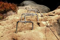Climbers ladder. Iron twisted rope fixed in block by screws snap hooks. The r Stock Photos