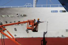 Man in cherrypicker painting the hull of a fishing vessel in a dockyard Port Stock Photos