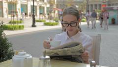 Young Woman Reading Newspaper and Drinking Tea At A Sidewalk Cafe Stock Footage