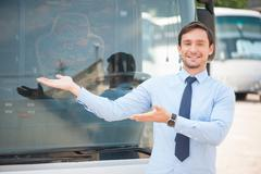 Stock Photo of Cheerful young man is advertising a public transport