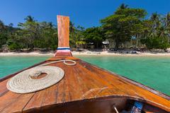 Thai boat on idyllic beach - stock photo
