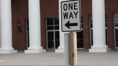 """One Way"" sign in front of a building Stock Footage"