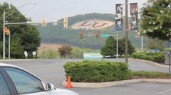 Cars drive through traffic light near LU's monogram - stock footage