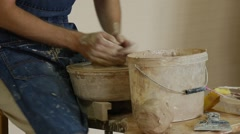 Potter Craftsman in Jeans Apron is Working Making Pot on Pottery Wheel Rotating Stock Footage