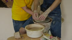 Craftsman in Jeans Apron Man is Working on Pottery Wheel Teacher Woman in Stock Footage