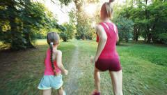 Athlets family mother and daughter running away from camera in the park Stock Footage