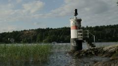 Small lighthouse with boat passing by in Mälaren Stock Footage