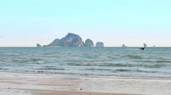 Longtail boat sails to the shore at the Ao Nang beach Stock Footage