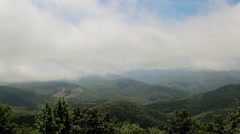 Low clouds on tall mountain tops Stock Footage