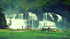 Ban Gioc Waterfall with visitors and bamboo rafts. Retro look. Vietnam Stock Footage