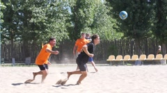 Football on the sand - tense moment chasing the ball - stock footage