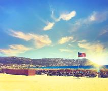 Patriotic USA background with American flag on the sandy beach at sunset. Vin - stock photo