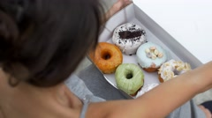 Fit woman opens box of donuts from above Stock Footage