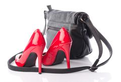 Red high heels shoes with a black handbag - stock photo