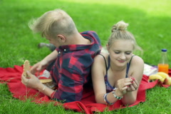 Couple lying on the blanket in the park and eating wafer-cake Stock Footage