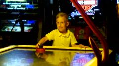 Happy and joyful little boy playing air hockey Stock Footage