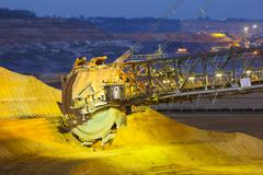 A giant Bucket Wheel Excavator in a lignite pit mine at night - stock photo