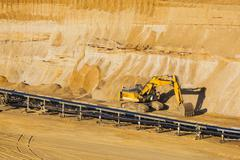 A small excavator at parked in a lignite pit mine - stock photo