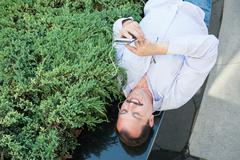 Urban man using smart phone outside using app on 4g wireless device wearing h - stock photo