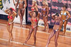 Female bodybuilders in abs and thighs pose on stage Stock Photos