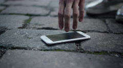 Girl is Picking up a Broken Mobile Phone on Street. Stock Footage