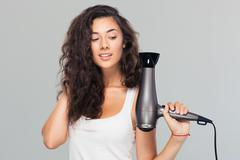 Smiling young woman holding hairdryer - stock photo
